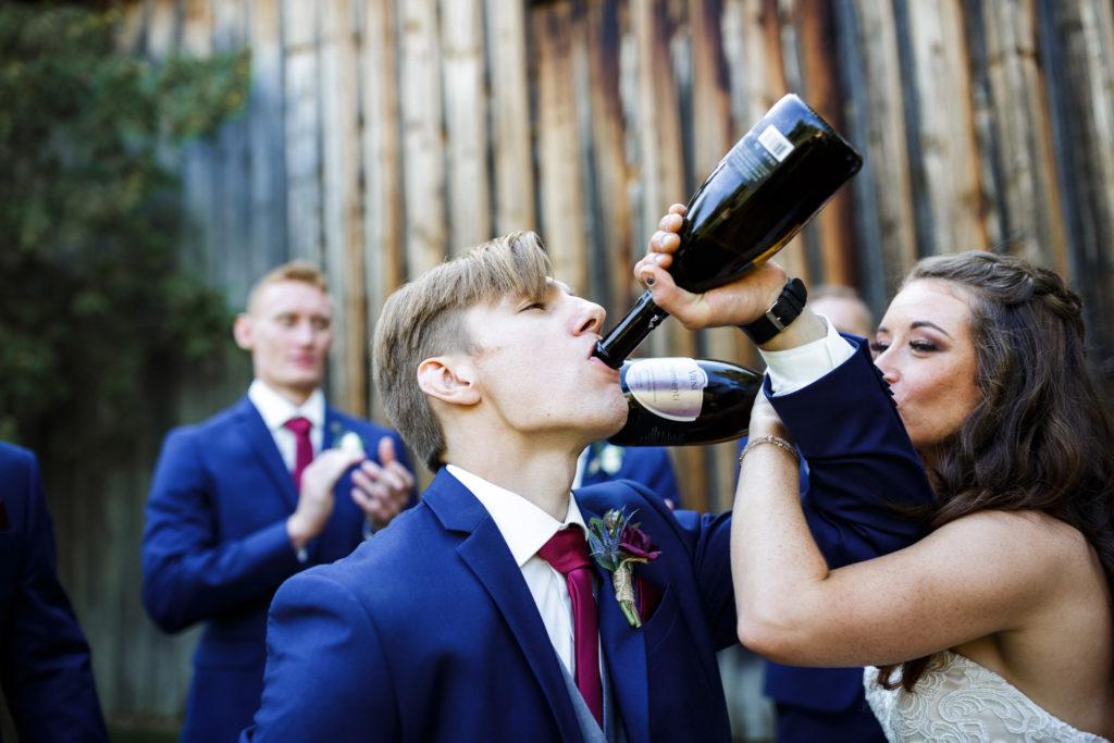 playful bride groom balls falls drinking wine barn wedding blue suit photographer