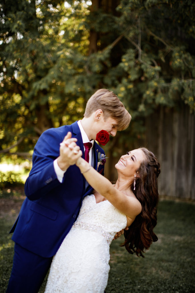 funny wedding photo bride groom hold rose in mouth dance balls falls wedding photographer